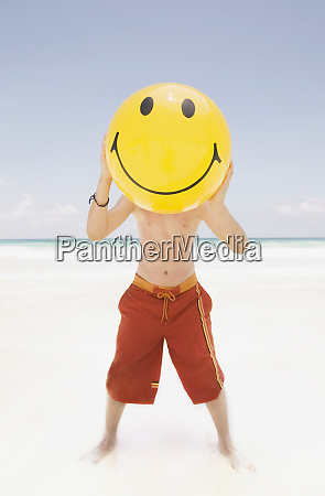 young boy holding a smiley face