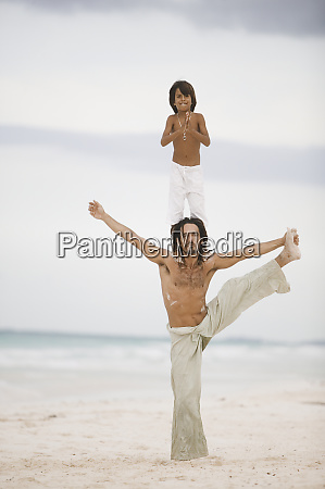 son standing on his fathers shoulders