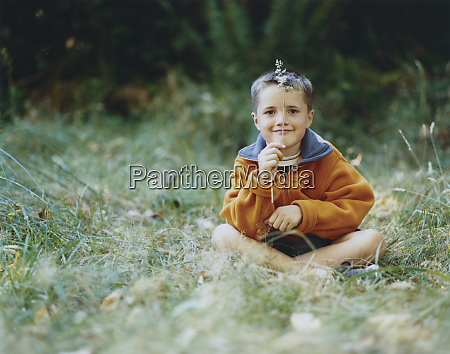 a young boy sits in field