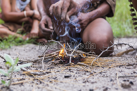 close up of bushman creating fire