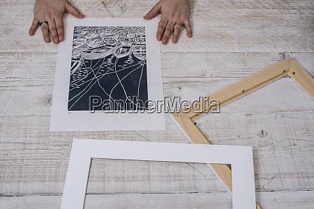 a person framing a lino cut