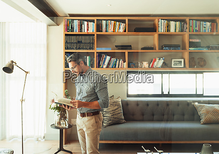man reading book in modern living