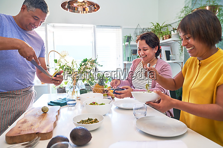 mature friends cooking in kitchen