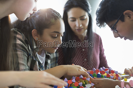 curious students examining dna model in
