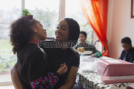 affectionate mother and daughter wrapping christmas