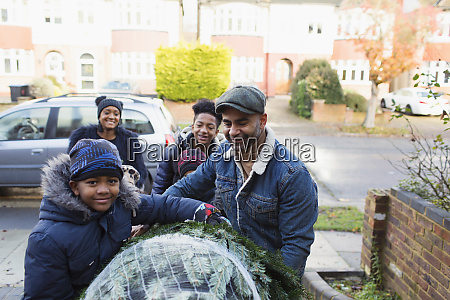 portrait happy family carrying christmas tree