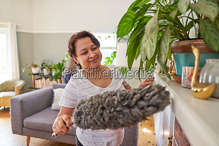 mature woman with duster dusting living