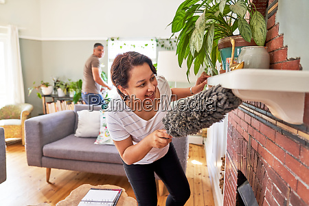 mature woman with duster dusting fireplace