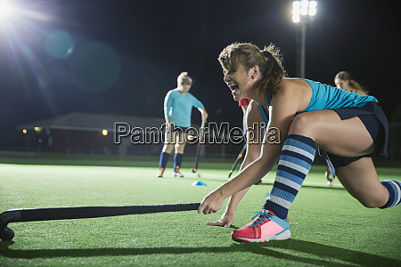 determined female field hockey player reaching