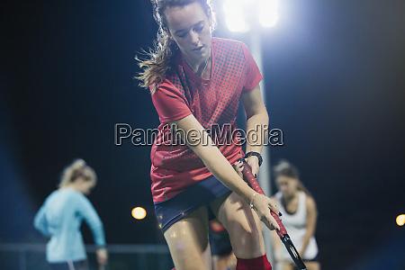 focused female field hockey player practicing