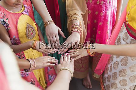 indian women in saris joining hands