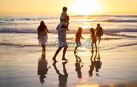 family wading in surf on idyllic