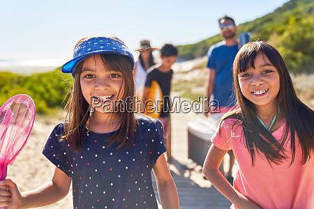portrait happy sisters on sunny beach