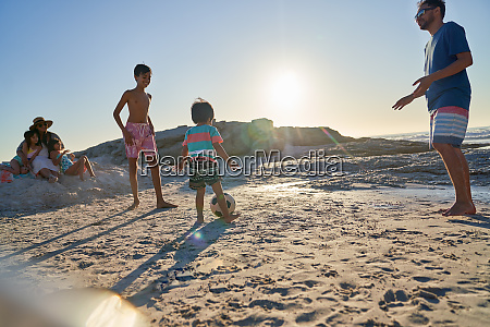 family playing soccer on sunny beach