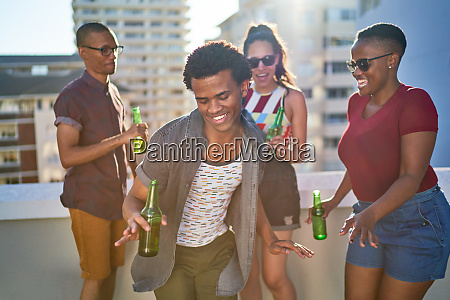 carefree young friends drinking beer on