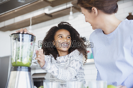 enthusiastic daughter helping mother making healthy