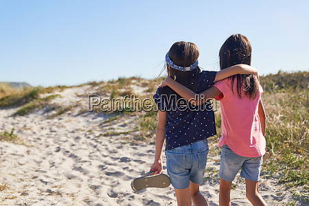 affectionate sisters walking on sunny beach