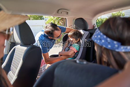 father securing son in car seat