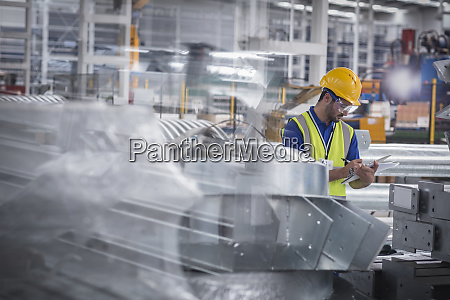 factory worker with clipboard inspecting steel