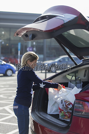 woman loading groceries into back of