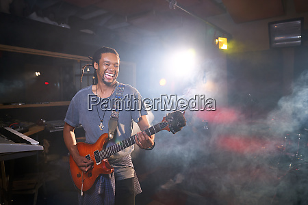 smiling male musician playing electric guitar