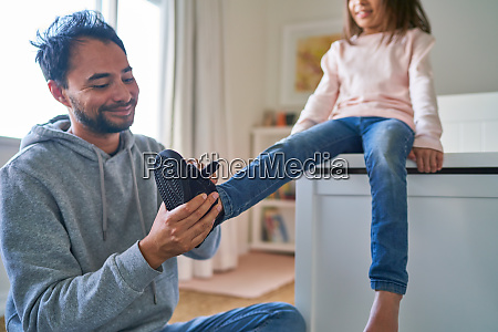 father helping daughter put on shoes