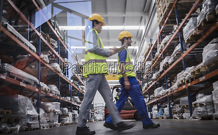 workers with clipboard walking in warehouse