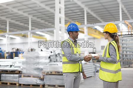 supervisors handshaking in warehouse