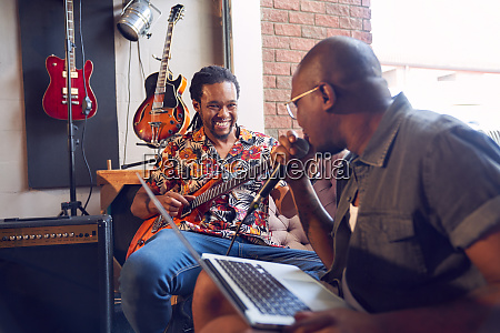 happy male musicians practicing in recording