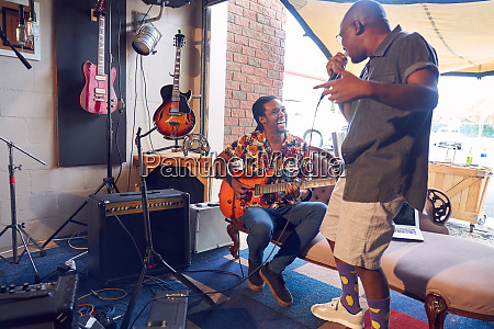 happy male musicians practicing in garage