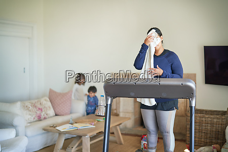 mother on treadmill wiping sweat from