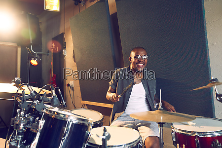 happy male musician playing drums in