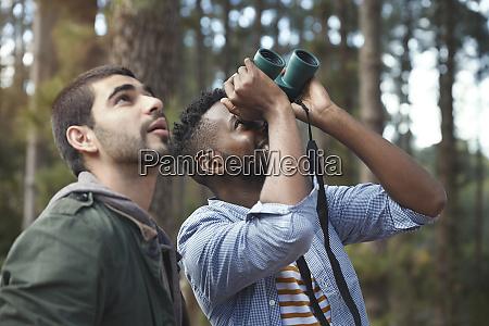 young men with binoculars bird watching