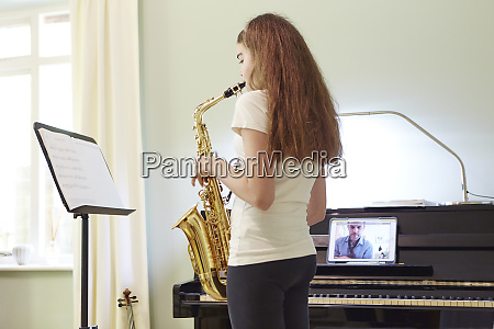 girl taking online saxophone lesson at