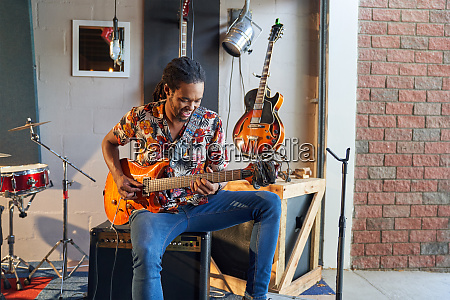 male musician playing electric guitar in
