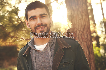 portrait confident young man in woods