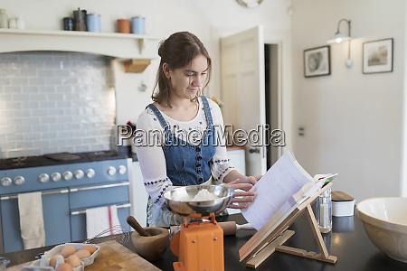 teenage girl with cookbook baking in