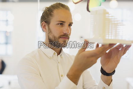 focused curious male architect examining model