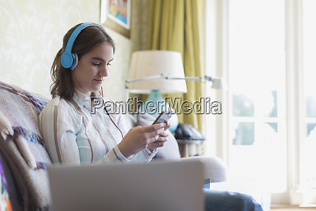 teenage girl with headphones and smart