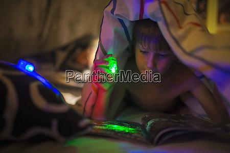 boy with green flashlight reading magazine