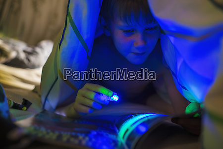 boy with black light reading magazine