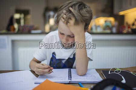 focused boy doing homework at table