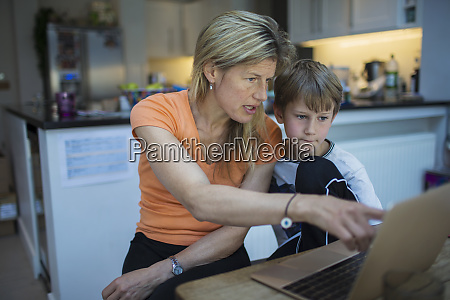 mother helping son with homework at