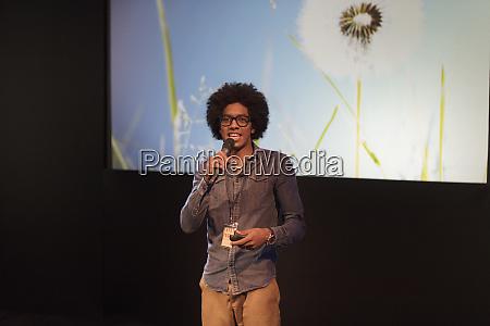 portrait male speaker with microphone talking