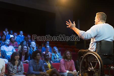 speaker in wheelchair on stage talking