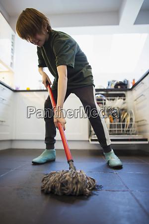 boy mopping kitchen floor