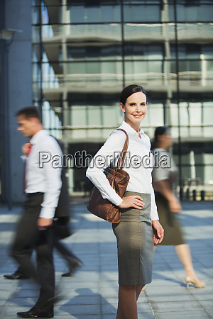 smiling businesswoman on urban sidewalk
