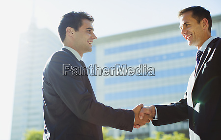 smiling businessmen shaking hands outside highrise