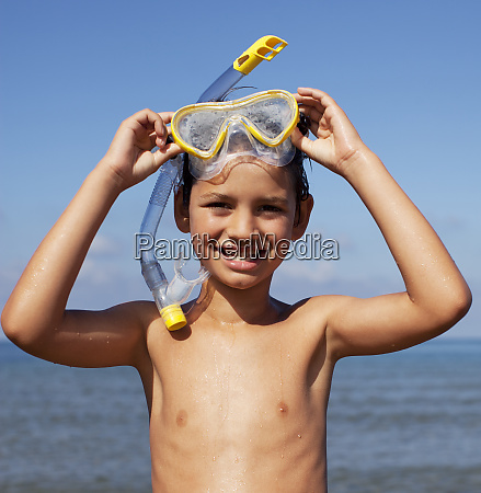 smiling boy removing snorkel and goggles