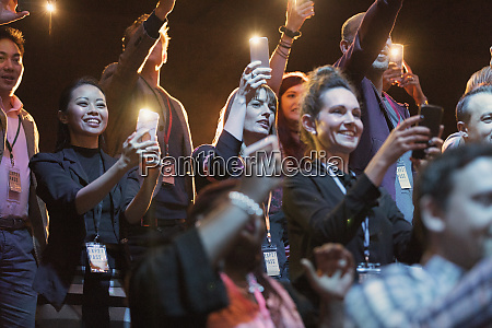 smiling audience with camera phone flashlights